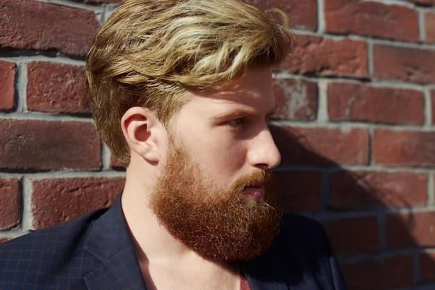 Hipster barbudo guapo con emoción seria en la pared de ladrillo rojo
