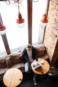 Hipster barbudo usando laptop en café