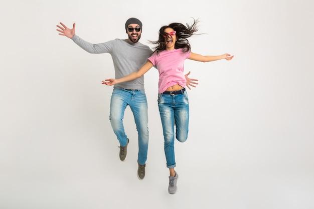 Hipster elegante pareja saltando aislado, mujer emocional muy sonriente y hombre vestido con jeans, activo y positivo, divirtiéndose juntos