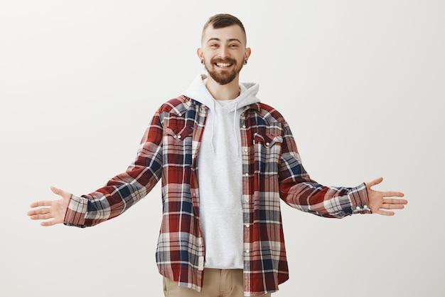 Hipster feliz amistoso extiende las manos hacia los lados y saluda a la gente, sonriendo sorprendido