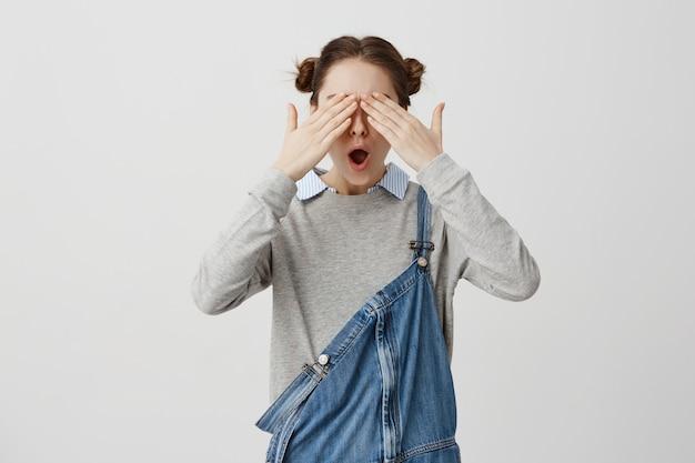 Hipster femenino que cubre los ojos con las manos reaccionando emocionalmente en felicitaciones. mujer guapa que anticipa algo con los ojos cerrados mientras está de pie sobre la pared en blanco. lenguaje corporal