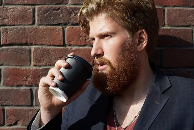 Hipster guapo bebe café al aire libre con pared de ladrillo rojo