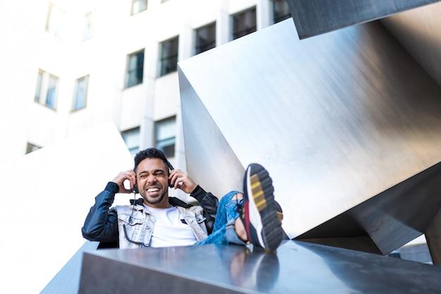 Hipster guapo guy escuchar música en auriculares y sonriendo.