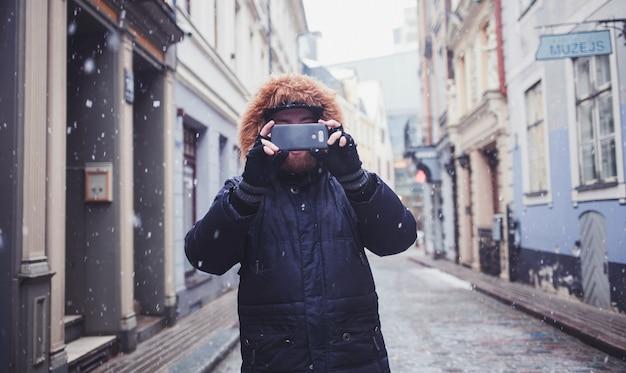 Hipster hombre con barba haciendo fotos en la ciudad vieja
