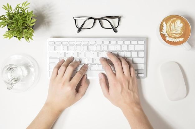 Hipster hombre está escribiendo en el teclado de la computadora, vista desde arriba.