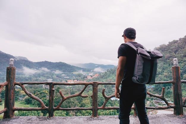 Hipster hombre guapo con mochila mirando de increíble paisaje en la cima de la montaña