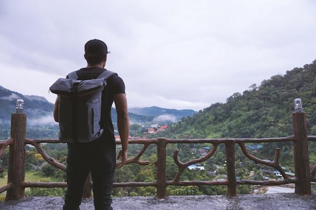 Hipster hombre guapo con mochila mirando de increíble paisaje
