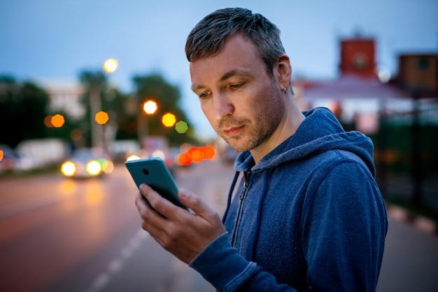 Hipster hombre hablando por un teléfono móvil por la noche en la ciudad.
