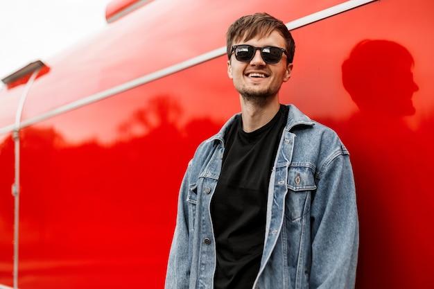 Hipster joven alegre con barba con una sonrisa positiva en una camiseta con una chaqueta de mezclilla de moda en una camiseta posando cerca de un edificio de metal rojo en la ciudad. chico urbano feliz en la calle.