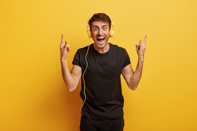 Hipster joven alegre escucha música rock en auriculares estéreo