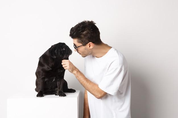 Hipster joven guapo con gafas, acaricia a su perro, mirándose, de pie sobre fondo blanco.