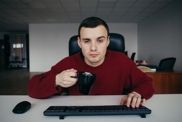Hipster joven sentado en el trabajo y tratando de no quedarse dormido con una taza de café en la mano.