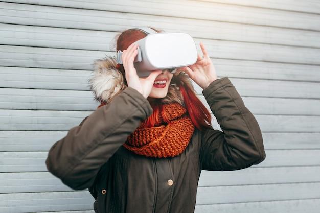 Hipster jovencita juega la aplicación de juegos móviles de realidad virtual en el teléfono inteligente conectado a las modernas gafas vr al aire libre