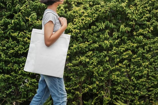Hipster mujer con bolsa de algodón blanco en el parque