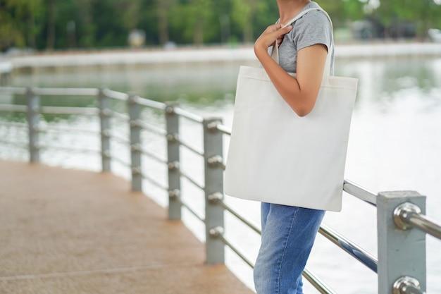 Hipster mujer sosteniendo la bolsa de asas blanca