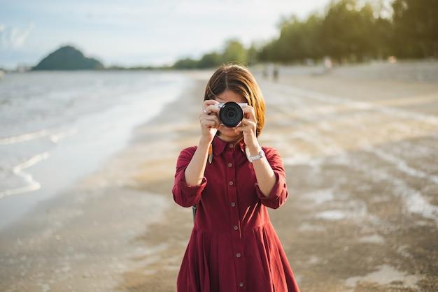 Hipster mujer toma una foto en la playa junto al mar