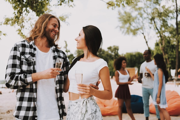 Hipster pareja enamorada bebe champán en la playa