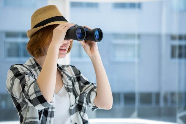 Hipster de pelo rojo mirando a través de binoculares delante de una ventana