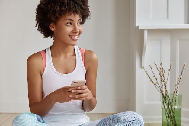 Hipster de piel oscura positiva actualiza la notificación en el nuevo teléfono celular, se sienta en el piso con las piernas cruzadas, mira a un lado,