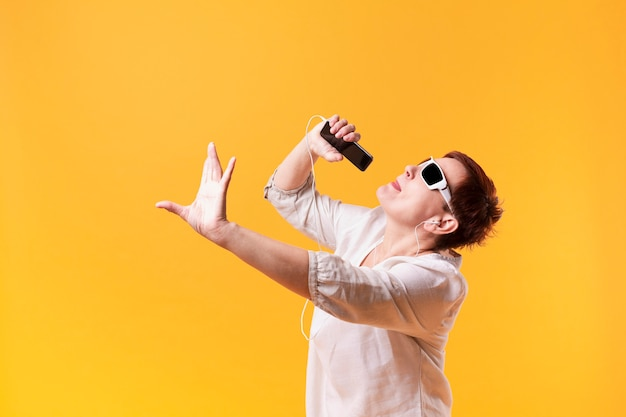 Hipster senior femenino bailando y cantando