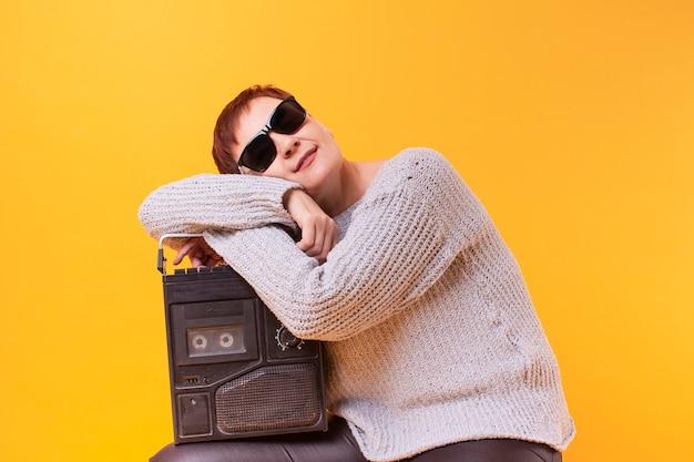 Hipster senior mujer descansando sobre un reproductor de cassette vintage