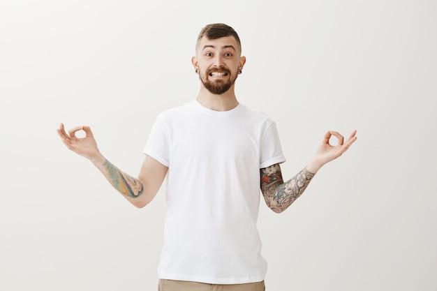 Hipster sonriente alegre con tatuajes meditando, practica yoga