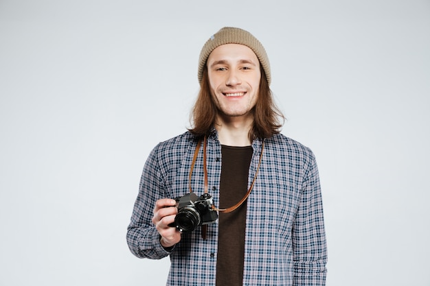 Hipster sonriente con cámara retro