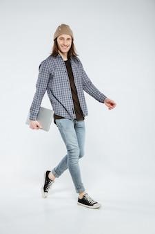 Hipster sonriente caminando con laptop