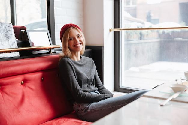 Hipster sonriente sentado en la cafetería