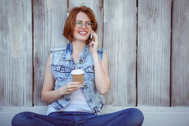 Hipster sonriente sosteniendo una taza de café y en el teléfono