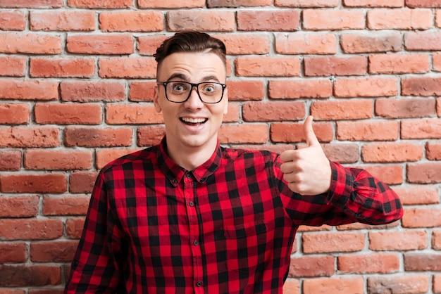 Hipster sorprendido feliz en vasos de pie cerca de la pared con el pulgar hacia arriba