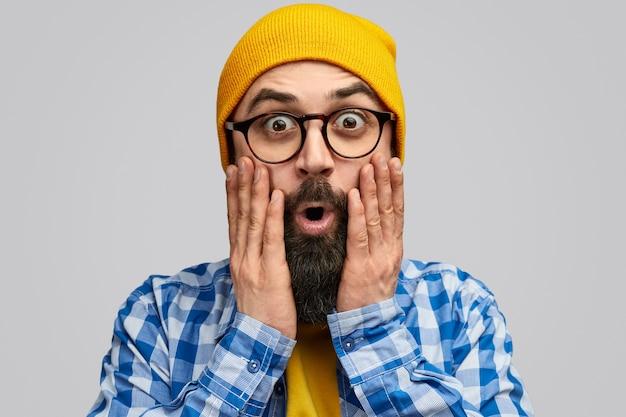 Hipster sorprendido mirando a cámara