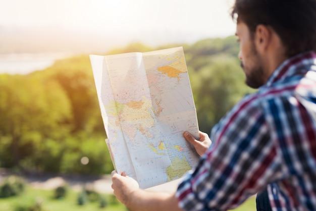 Hipster turista está caminando solo estudiando un mapa.