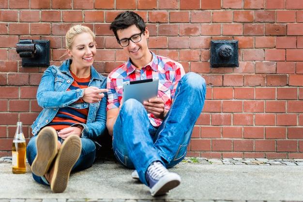 Hipster turistas planeando vacaciones en berlín con computadora pad