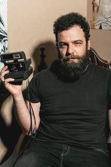 Hipster ubicando y sosteniendo una cámara fotográfica