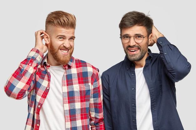 Los hipsters masculinos vacilantes se rascan la cabeza con expresiones desorientadas, no pueden tomar una decisión sobre cuándo comenzar a trabajar en el trabajo del proyecto