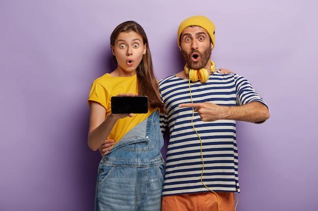 Los hiptsers emocionados y sorprendidos señalan la pantalla del teléfono inteligente moderno, muestran el espacio de la maqueta para su contenido promocional, se abrazan y miran con estupor, aislado sobre una pared púrpura. publicidad tecnológica
