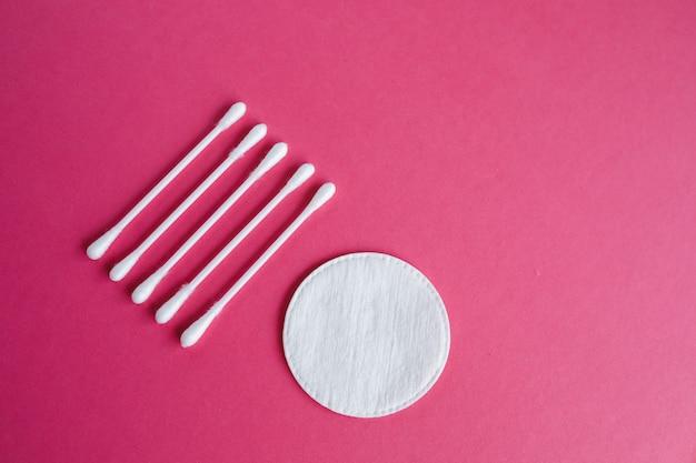 Hisopos de algodón y discos aislados sobre un fondo rosa. productos de higiene.