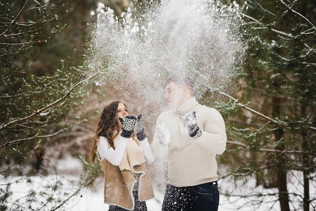 Historia de amor de invierno sobre hielo. amantes con estilo chico y chica en el bosque de invierno arrojan nieve y ríen