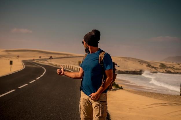 Hitcher people hombre caucásico para personas viajan concepto con mochila en lugar de playa de arena dersrt escénica al aire libre