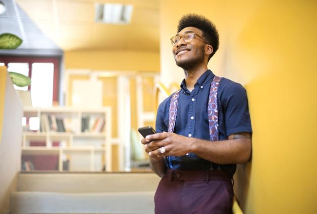Hnadsome guy sonriendo mientras chiecking su teléfono inteligente