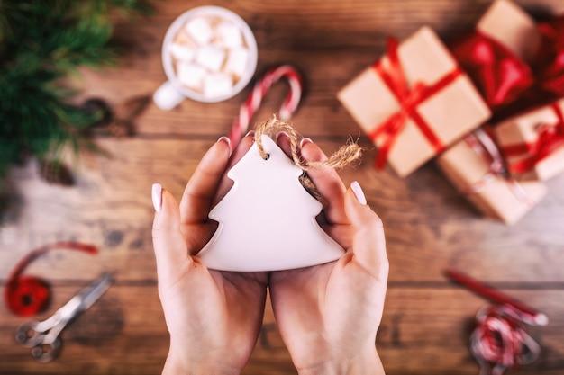 Hobby creativo las manos de la mujer muestran el juguete hecho a mano del árbol de navidad de las vacaciones de navidad