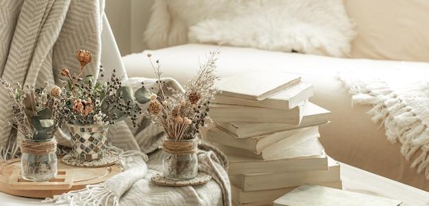 Hogar acogedor interior de la habitación con libros y flores secas en un jarrón.