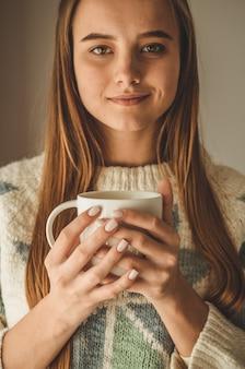 Hogar acogedor. mujer con taza de bebida caliente junto a la ventana. mirando la ventana y bebiendo té. buenos días con té. bastante joven relajante. concepto feliz.