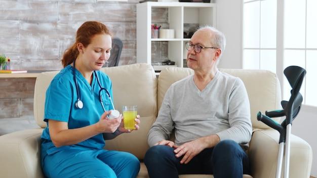 En el hogar de ancianos, la enfermera está dando pastillas diarias a un anciano con muletas a su lado. cuidador y trabajador social