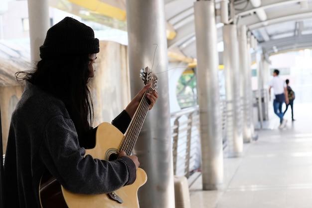 Sin hogar, levantarse, guitarra, cantar por donaciones.