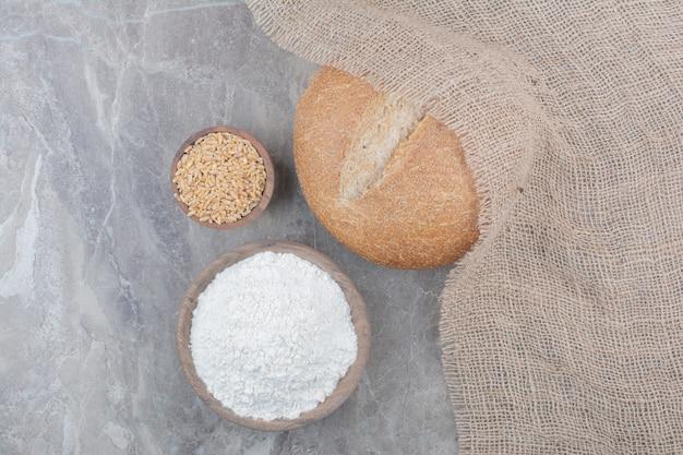 Una hogaza de pan blanco con granos de avena y harina sobre la superficie de mármol