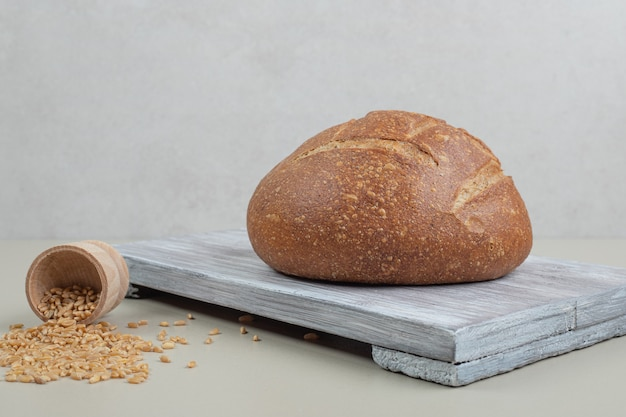 Hogaza de pan fresco con granos de avena sobre fondo blanco. foto de alta calidad