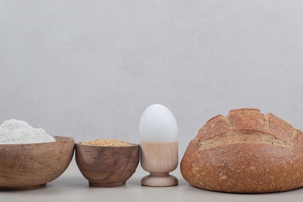 Hogaza de pan con huevo cocido y granos de avena. foto de alta calidad