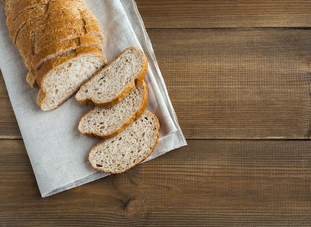 Hogaza de pan de trigo blanco con salvado sobre una servilleta plana yacía sobre una mesa de madera con espacio de copia